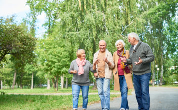 group of four people two mwn and two women walking together through a park