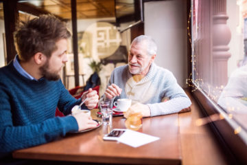 two men sitting together having a conversation over coffee. One younger in a blue jumper the other older with a beard in a grey jumper