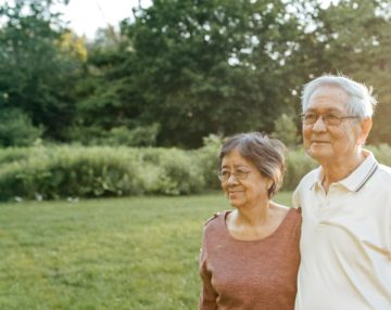 elderly couple, man and woman walking in a park with green grass and bushes in the background