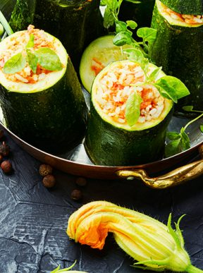 zucchini stuffed with rice in a bowl on a dark background