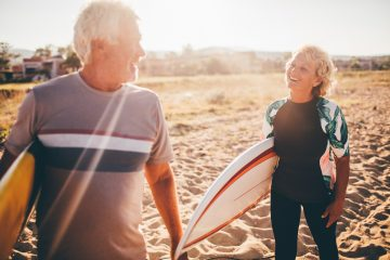 man and woman at the beach with their surfboards excited and getting ready to hit the waves