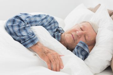 Man in bed in checked pyjamas sleepi