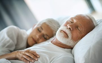 senior white haired contemporary-looking couple sleeping soundly