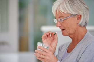 elderly woman taking reflux medication with a glass of water