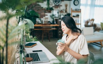 Asian woman working from home struggling with neck pain