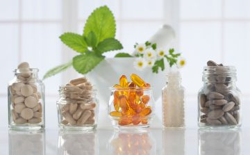herbal complementary medicines in glass jars in front of a white pestle and mortar containing mint leaves and chamomile flowers
