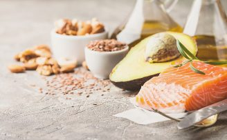 examples of healthy fats on a bench, includes salmon, avocado, nuts and olive oil