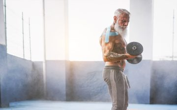 Bearded, tattooed older man in grey trackpants using a dumbell.