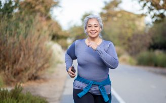 Happy middle-aged woman jogging down country lane