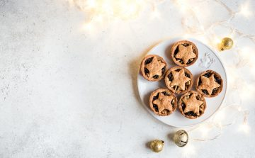 six mince pies on a white plate on a white marble surface surrounded by fairy lights, gold baubles and a gold christmas decorationbell