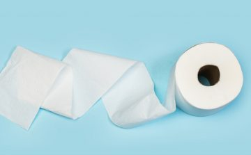 Unravelling white toilet paper on a blue background