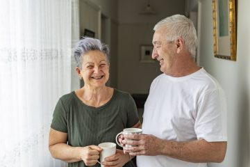 Happy senior couple standing together smiling enjoying a cup of teas