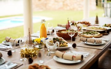 Festive christmas table with bon bons, wine glasses, a gravy boat on a sunny day
