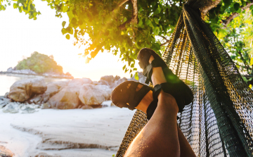 close up of male feet wearing sandals in a hammock at the beach