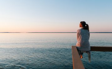 young woman looking out to sea at