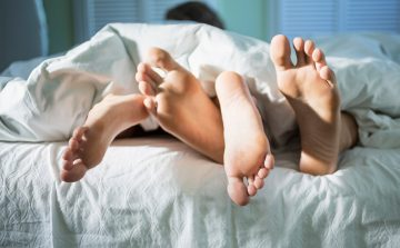 image of a young couple in bed with their feet entwined