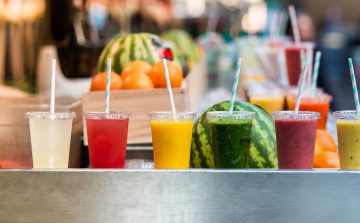 A row of different coloured fruit juices and smoothies in plastic see-through cups with straws