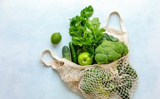 selection of healthy green fruit and veg in a strng bag
