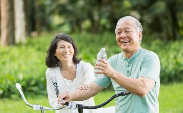 Couple riding bikes stop to have a drink of water