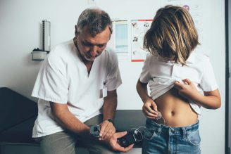 A doctor looks at the CGM readings of a child with diabetes
