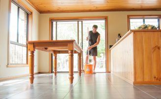 Young man cleaning dining room floor