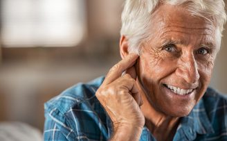 smiling senior man with hand to ear